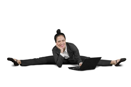 Happy business woman using a laptop computer while sitting in splits, isolated on white background Stockfoto
