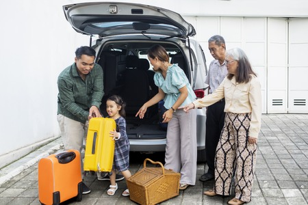 Picture of a multi generation family ready to trip while preparing suitcase into a car for holiday