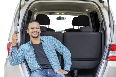 Picture of smiling Afro man holding a new car key while sitting in the car trunk, isolated on white background