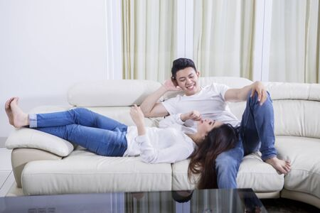Young couple enjoying leisure time together while chatting on the couch. Shot at home Stockfoto