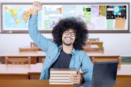 Excited Afro college student celebrating his success while studying with books and laptop computer in the classroom Stockfoto