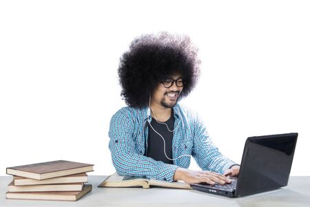 Frizzy male college student using a laptop and headset while studying in the studio, isolated on white background