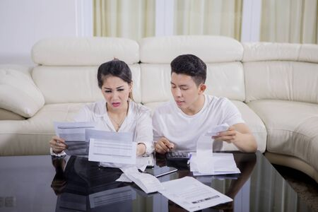 Picture of young couple looks stressed while checking their high expenses while sitting at home