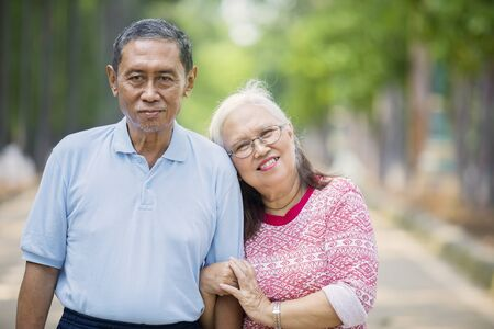Picture of happy old woman embracing her husband while standing on the road Stockfoto