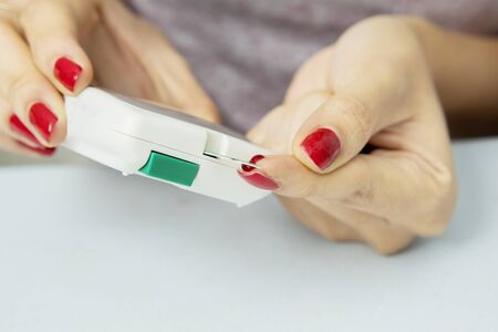 Hands of unknown woman checking blood sugar while using a digital glucometer Stockfoto