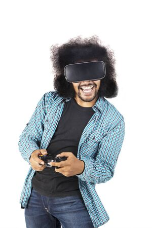 Portrait of happy Afro man using virtual reality glasses and joystick for play video game, isolated on white background Stockfoto