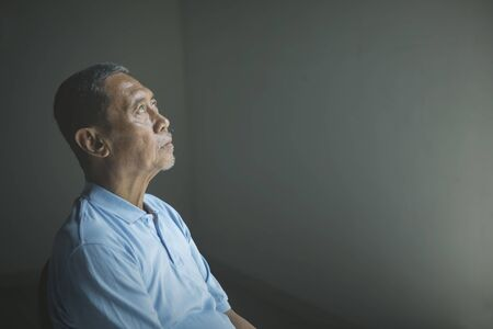 Picture of sad old man daydreaming and sitting alone in the dark room Stockfoto