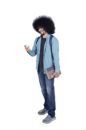 Full length of Afro male college student using his smartphone while holding books and standing in studio, isolated on white background