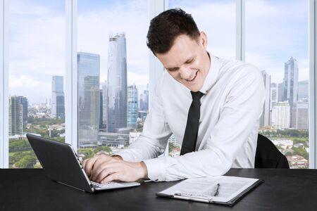 Picture of Caucasian businessman doing paperwork near the window and typing on laptop