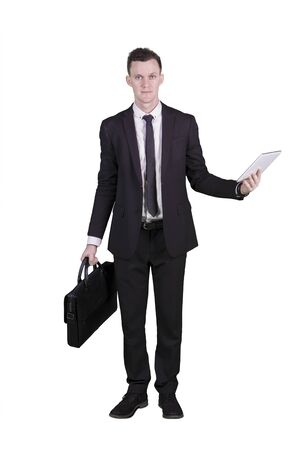 Full length of Caucasian businessman holding a briefcase and using a digital tablet in the studio