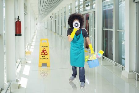 Male janitor shouting with a megaphone while holding a bucket and standing near a wet floor sign in the train station corridor Stockfoto