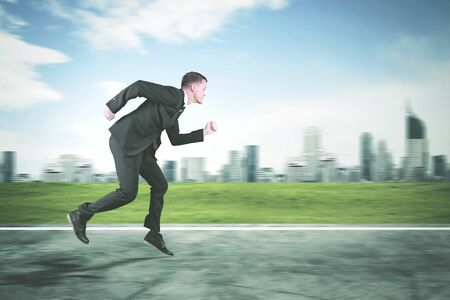 Side view of American businessman wearing formal suit and sprinting on the road with modern city background Stockfoto