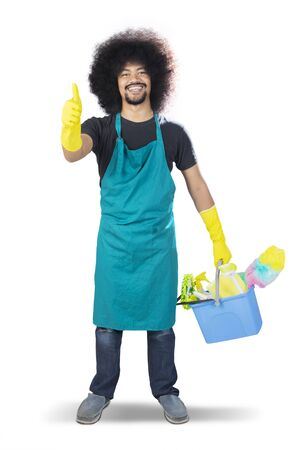 Full length of happy male janitor showing thumbs up and standing with cleaning equipment in the studio