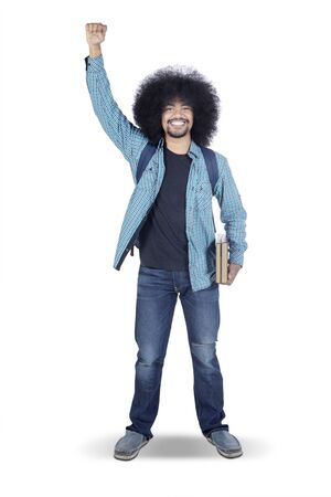 Portrait of Afro male college student lifts his clenched fist in the studio, isolated on white background