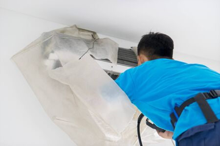 Close up of unknown male worker washing an air conditioner from dust with spray