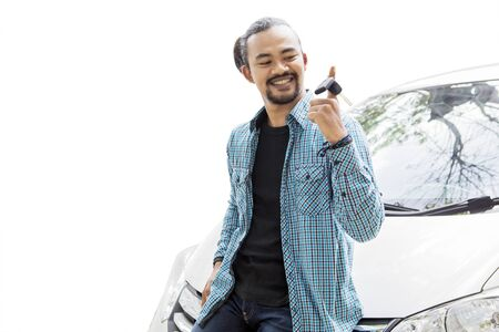 Image of young African man looks happy while twisting a new car key and leaning on his dream car, isolated on white background