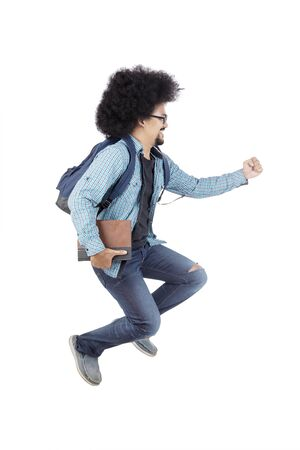 Side view of Afro male college student gesturing sprints in the studio, isolated on white background Stock Photo - 124525861