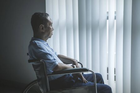 Picture of sad old man sitting in the wheelchair while looking out the window in the retirement home