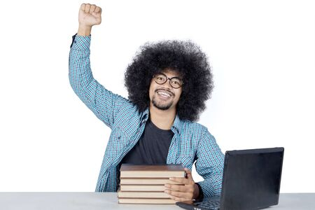 Afro male college student celebrating his success by lifting a clenched fist while studying in the studio