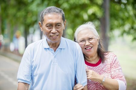 Elderly man embraced by his wife while smiling at the camera. Shot in the road