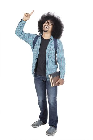 Full length of Afro male college student getting inspiration while standing in the studio, isolated on white background