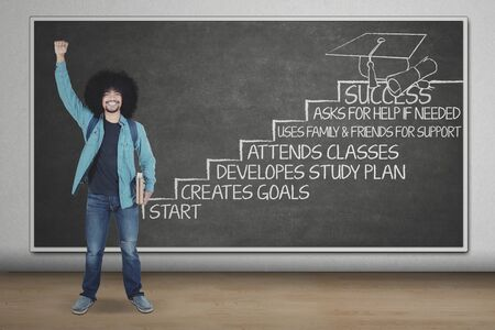 Picture of excited Afro college student standing with strategy to success in the staircase. Shot in the classroom Stock Photo
