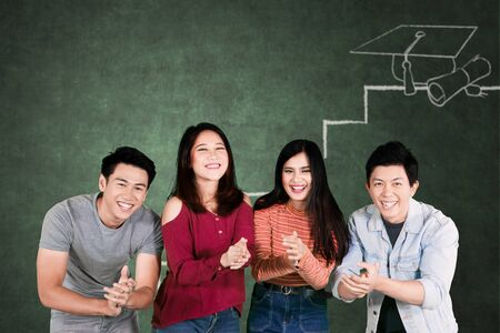 Group of happy college students applauding at the camera while celebrating graduation in the classroom Stockfoto