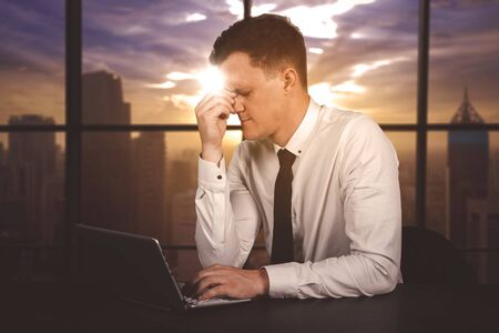 Caucasian businessman looks stressed while overworking in the office. Shot at dusk time