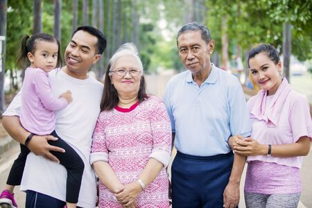 Picture of smiling three generation family looking at the camera while standing on the road. Shot at the park
