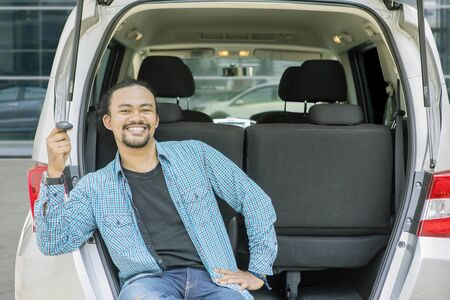 Picture of happy young man holding a new car key while sitting in the car trunk. Shot in showroom Stockfoto