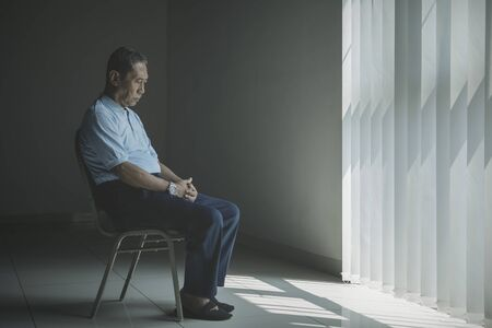 Close up of lonely aged man looks sad while sitting on the chair near the window