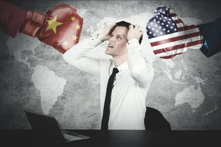 Picture of Caucasian businessman looks depressed with trade war between USA and China Stockfoto