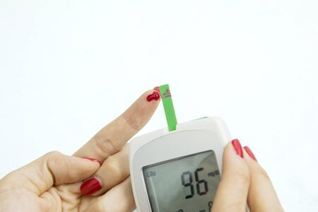 Hands of unknown woman checking her blood sugar by using a digital glucometer Stockfoto