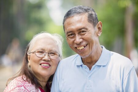 Close up of Asian old couple smiling at the camera while standing in the park Stockfoto