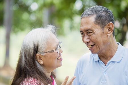Close up of cheerful old couple chatting together and standing in the park