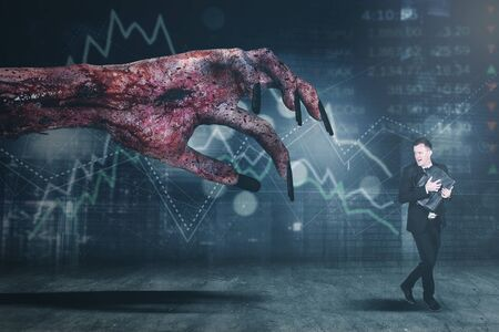 Picture of male broker looks scared while running away from creepy hand with crisis stock market background