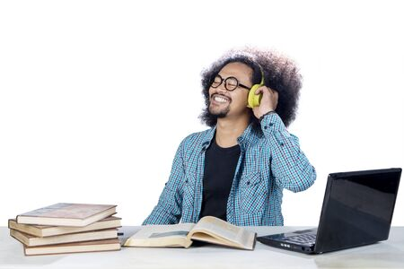 Picture of Afro male college student enjoying music by using a headset while studying in the studio