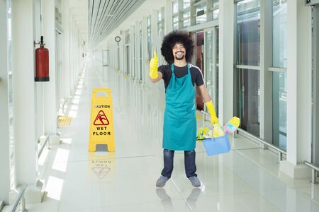 Afro male janitor showing thumbs up and standing with cleaning equipment in the train station corridor
