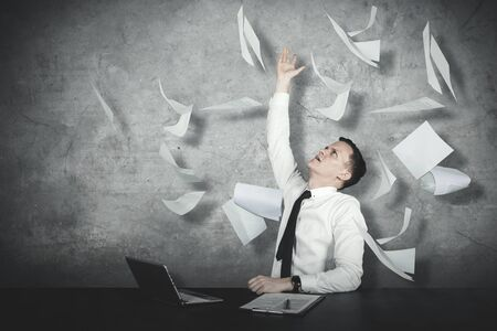 Picture of American businessman looks stressed while throwing papers Stockfoto