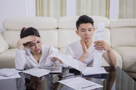 Picture of worried young couple calculating their high expenses while sitting at home