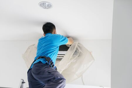 Rear view of unknown male worker cleaning an air conditioner from dust Stockfoto