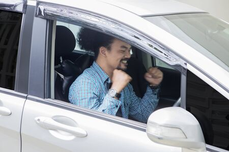 Picture of a young African man expressing happy while sitting in his new car