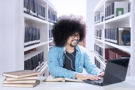 Picture of a frizzy male college student using a laptop and earphone while studying in the library