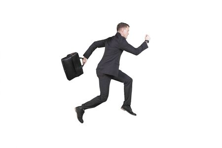 Side view of Caucasian male manager holding a suitcase while sprinting in the studio, isolated on white background