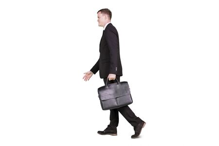 Side view of male manager walking forward in the studio while carrying a briefcase