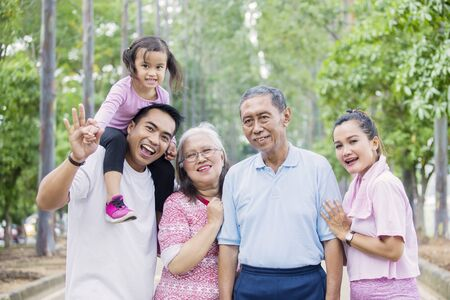 Picture of cheerful multi generation family looking at the camera while standing on the road. Shot at the park