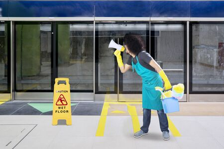 Male janitor using a megaphone to speak and standing near a wet floor sign in the train station