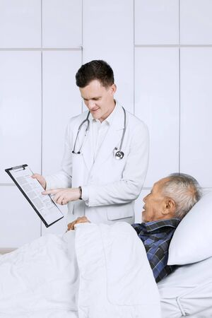 Caucasian male doctor showing a clipboard to his elderly patient and explaining test result in the hospital Stockfoto