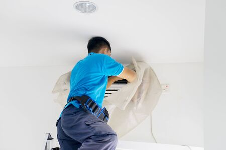 Rear view of unknown male worker fixing an air conditioner from dust