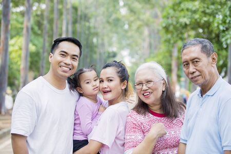 Picture of Asian three generation family smiling at the camera while standing on the road. Shot at the park